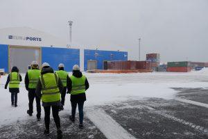 Turva-asuiset henkilöt satmalaueella lumisessa ympäristössä.
